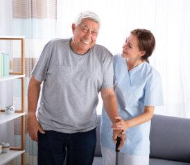 caregiver assisting the senior man