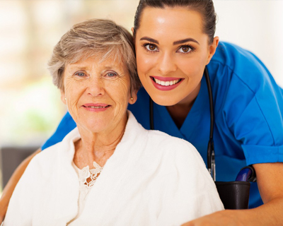 a nurse and a senior woman smiling