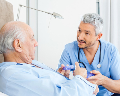 a caregiver giving a senior man his pain medication