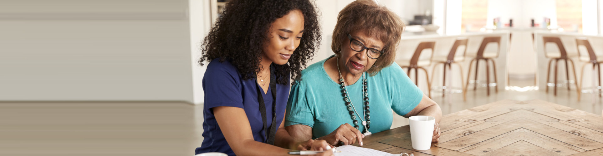 caregiver assisting the elder woman about the documents